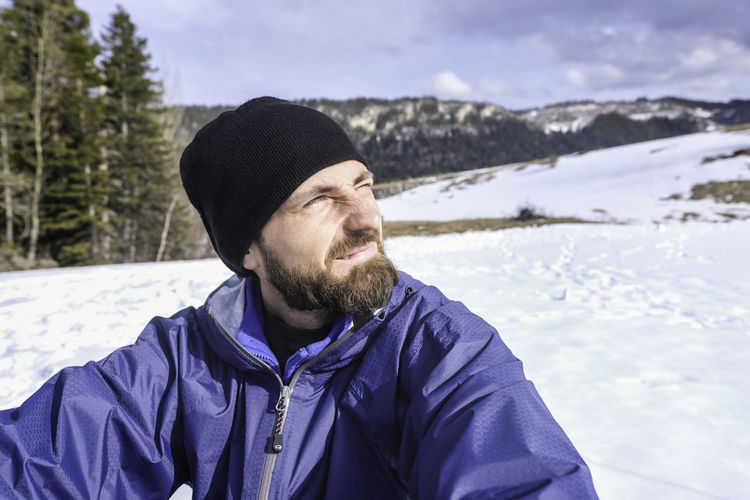 Man Sitting On Snow Field