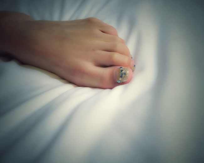 Cropped Woman Foot With Nail Art On Bed