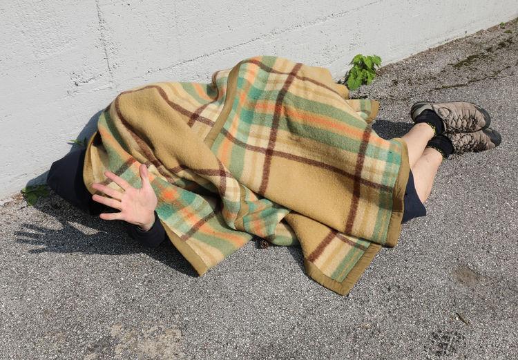 High angle view of man sleeping on footpath