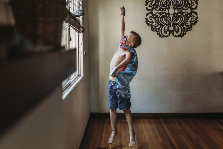 Full length of boy standing against wall at home