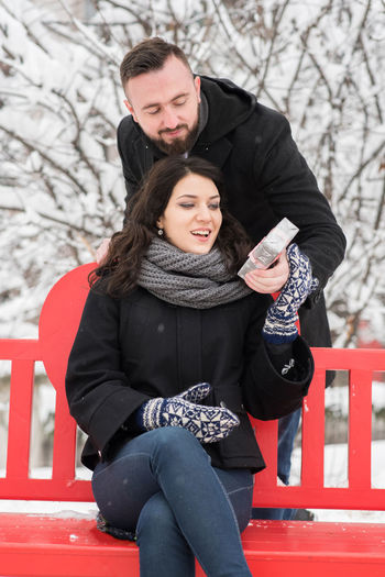 Young man giving surprise to woman sitting on bench during winter