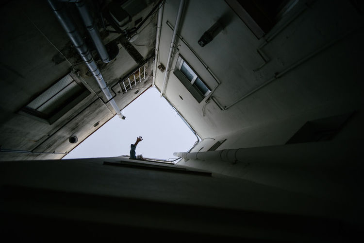 Low angle view of silhouette person standing in building