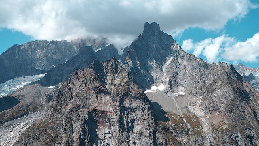 Panoramic view of  aiguille noire de peuterey and mont blanc behind the clouds, alps italy.