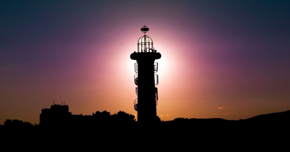 Low angle view of silhouette lookout tower against clear sky at dusk