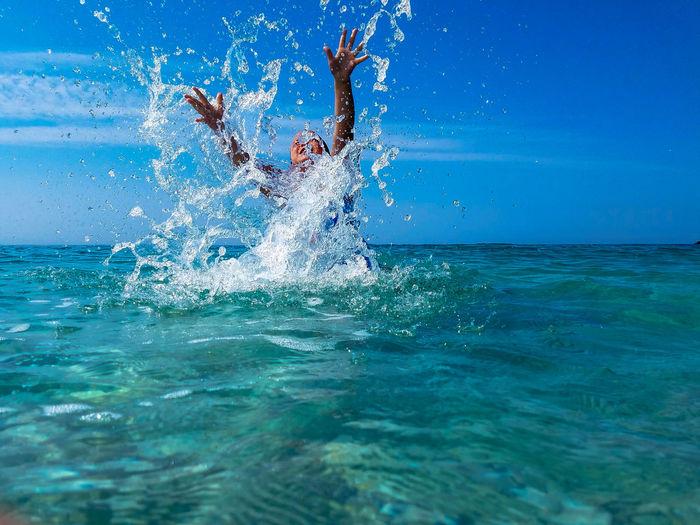 Boy swimming in sea against blue sky