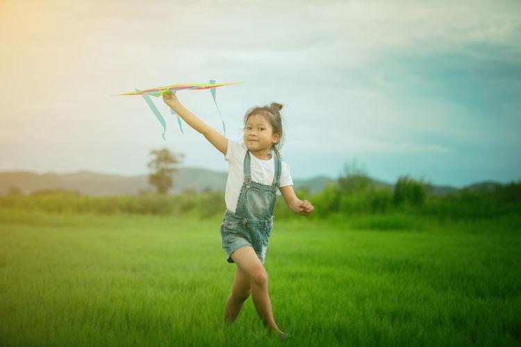 Full length of girl carrying kite on grass field