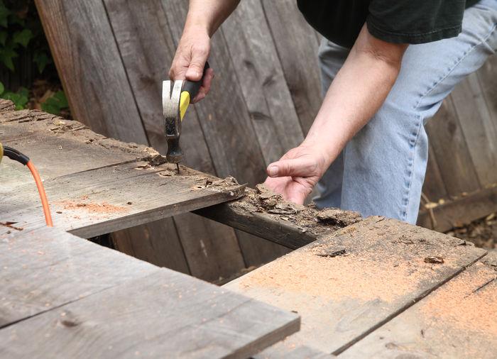 Man hammering nail on wooden plank
