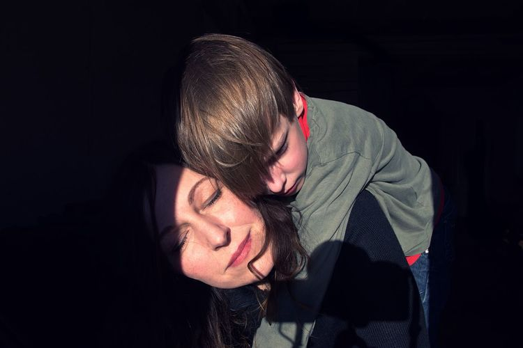 Sunlight Falling On Mother Piggybacking Son In Darkroom
