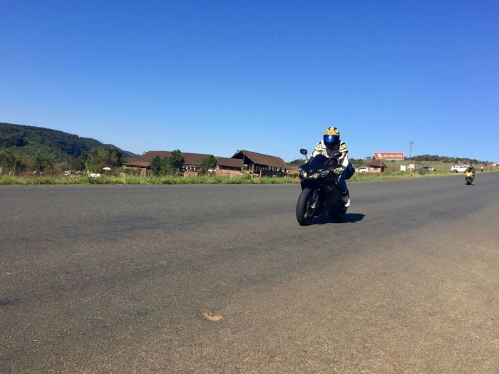 Man riding motorcycle on road against clear blue sky