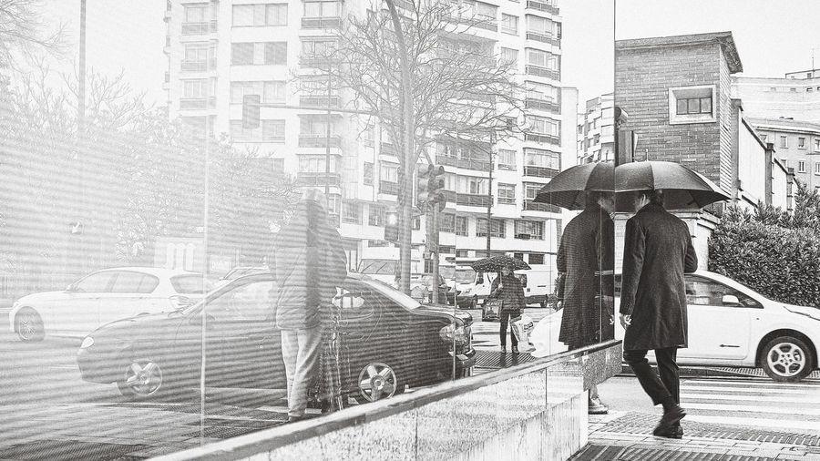 Man walking on wet street in city