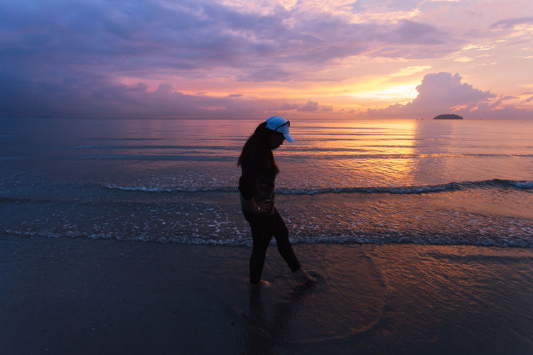 Woman standing on beach against sky during sunset