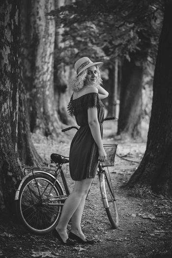 Side view portrait of woman standing with bicycle against trees in forest