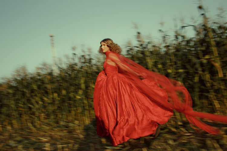 Side view of woman with red dress running against plants
