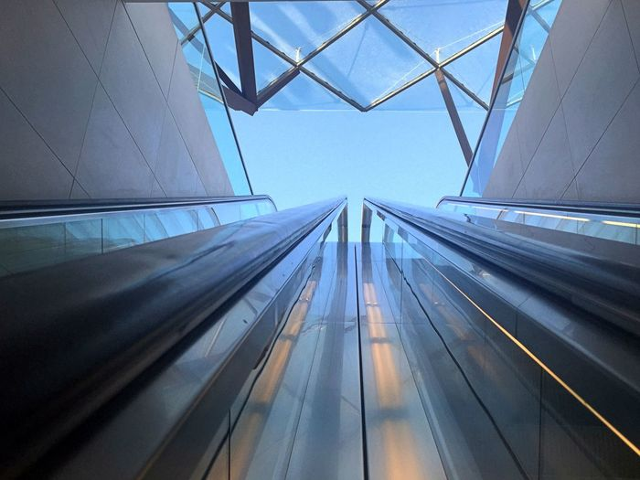 Low angle view of escalator railings against sky in city
