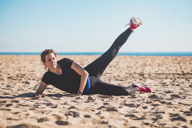Full length of woman exercising while lying on beach against sky