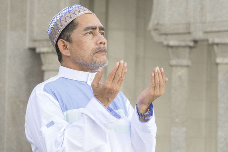 Close-Up Of Man Praying While Standing At Mosque