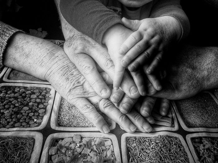 Stacked Hands Of Family On Table At Home