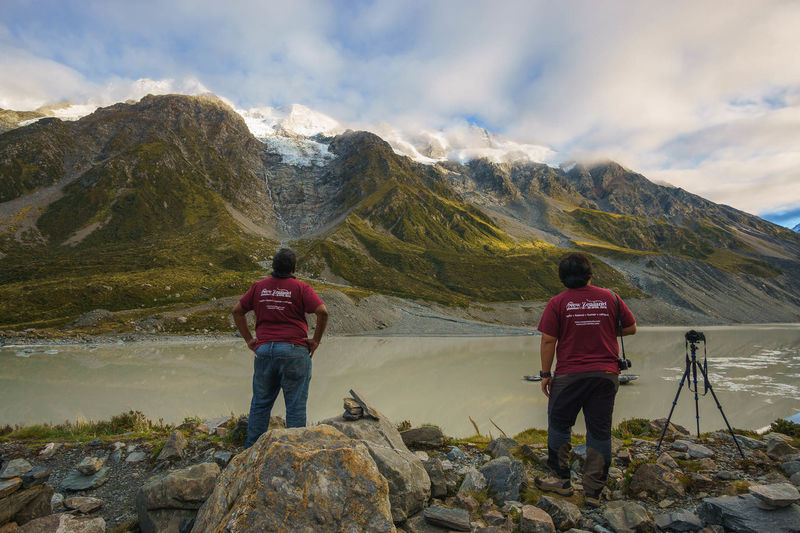 Rear view of men standing on rocks against mountains