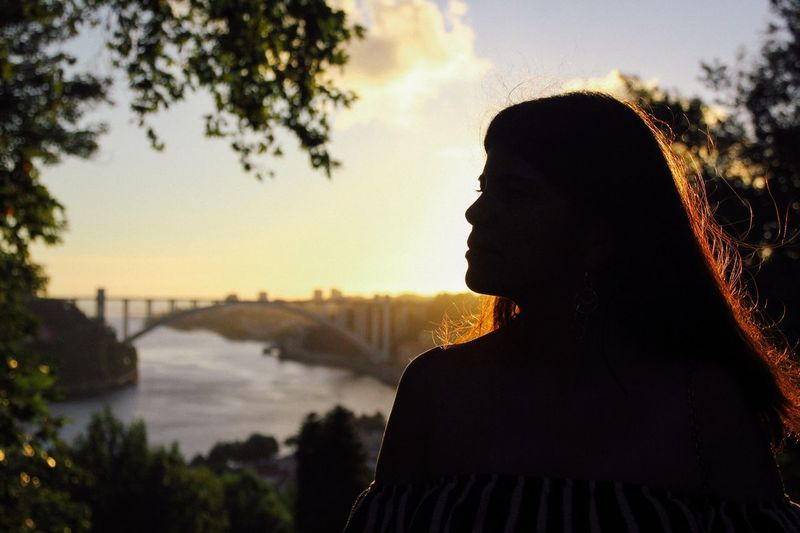 Close-up of silhouette woman standing against river at sunset