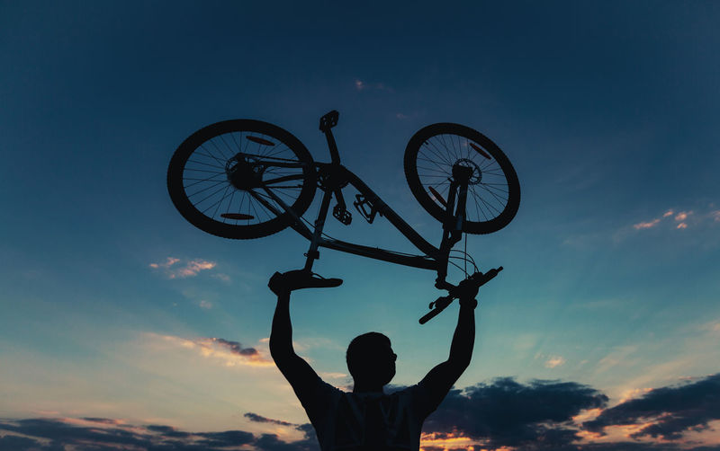 Low angle view of silhouette man holding bicycle against sky