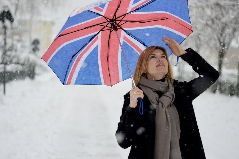 Woman with umbrella standing in snow
