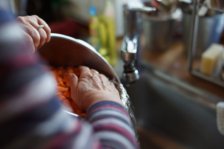 Close-up of woman washing sliced carrots