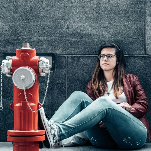 Beautiful Woman Sitting By Fire Hydrant Against Wall