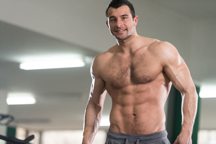 Portrait of smiling shirtless man standing in gym