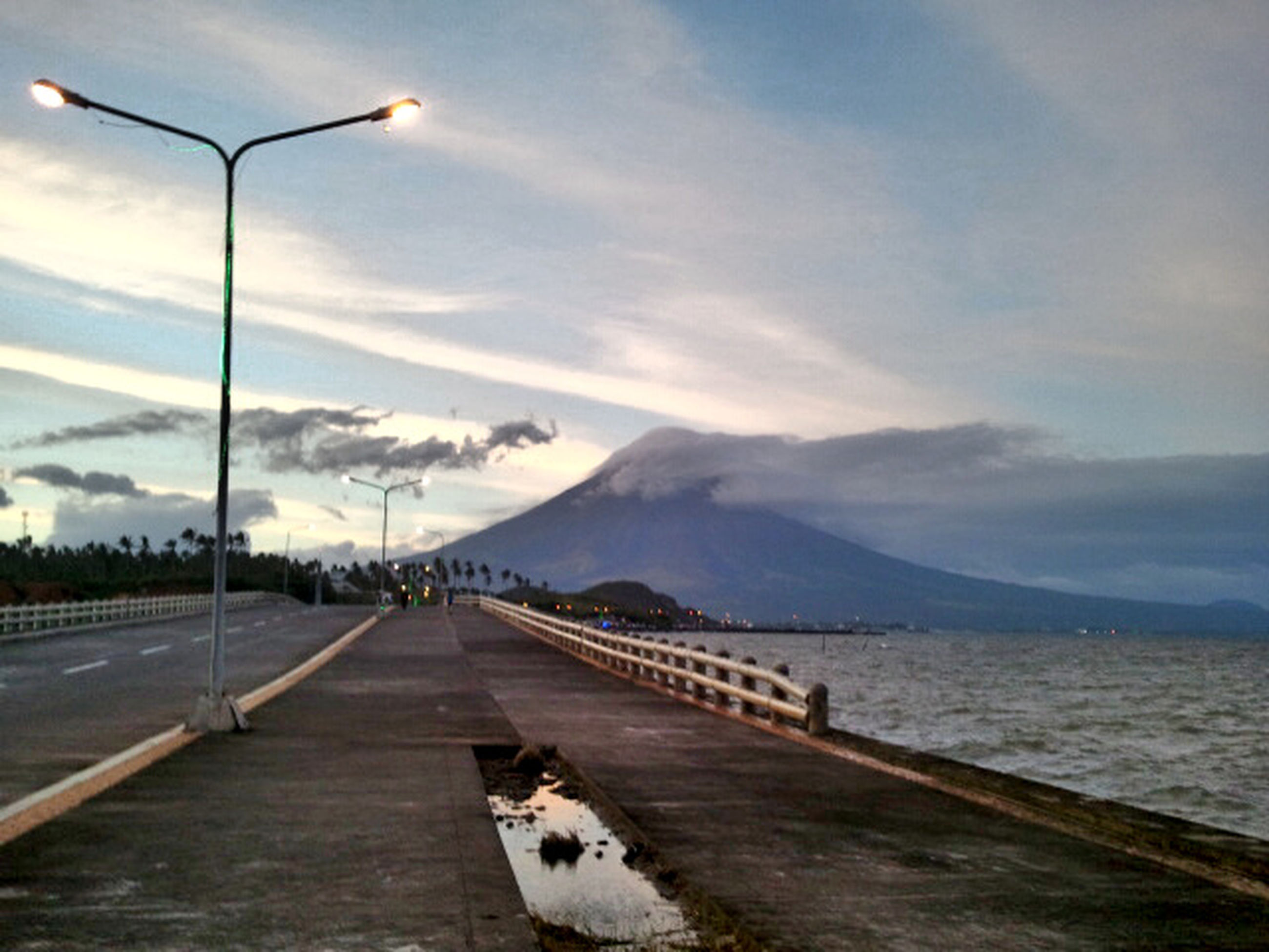 sky, the way forward, cloud - sky, water, sea, cloud, mountain, tranquil scene, transportation, cloudy, diminishing perspective, tranquility, scenics, beauty in nature, vanishing point, nature, pier, outdoors, street light, idyllic