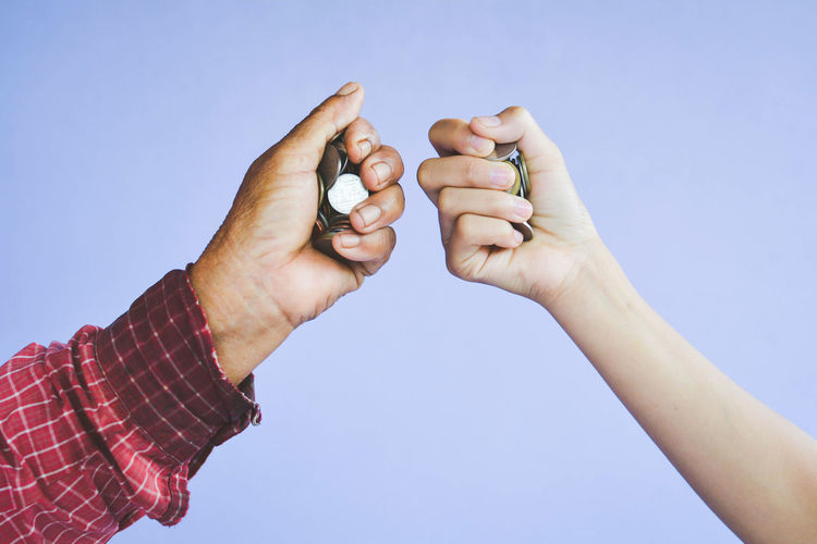 Cropped Image Of Hands Holding Coins Against Purple Background