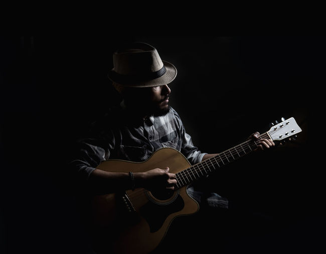Acoustic Guitar Artist Arts Culture And Entertainment Black Background Clothing Guitar Guitarist Hat Indoors  Men Music Musical Equipment Musical Instrument Musician One Person Performance Playing Plucking An Instrument Rock Music Skill  String Instrument Studio Shot Three Quarter Length