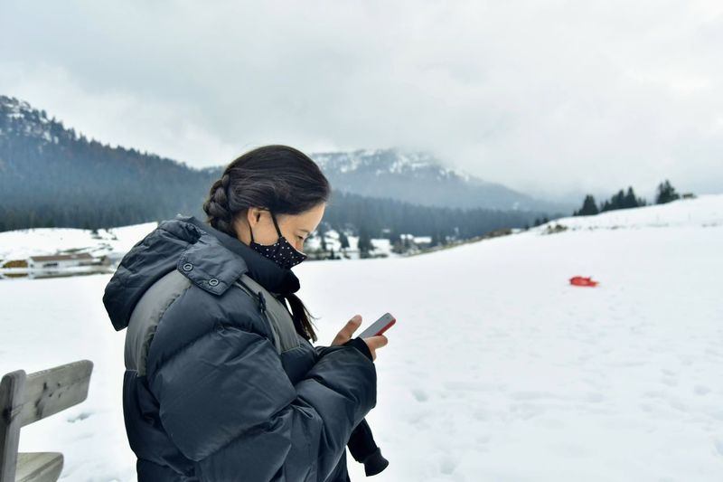 Side view of woman on snow covered mountains
