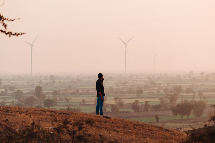 Man standing on hills against windmills