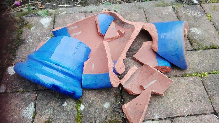 Storm damage. A broken blue clay planter Broken Planter Potted Plant Damaged Storm Garden Object Blue Clay Backyard Patio Potsherds Shard Blue High Angle View Close-up Colorful Botanical Handmade ArtWork