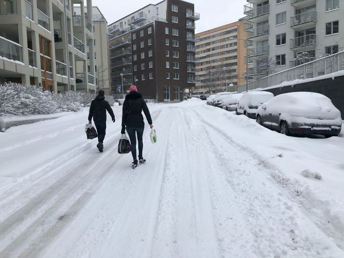 Rear view of people walking on snow covered buildings in city