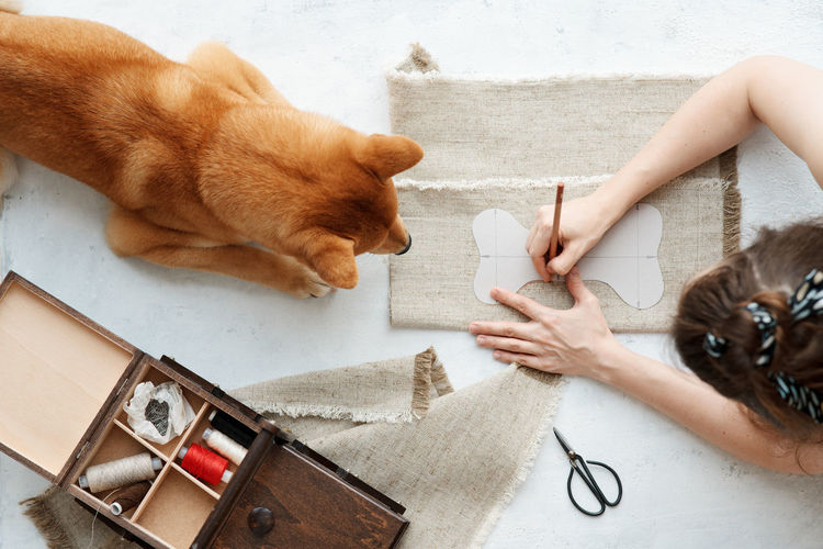 Top view of woman making eco friendly textile bone for her domestic dog. diy toys and treats