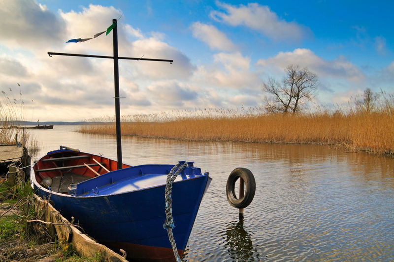 Wide Shot Of Boat Moored At Lake Against Cloudy Sky