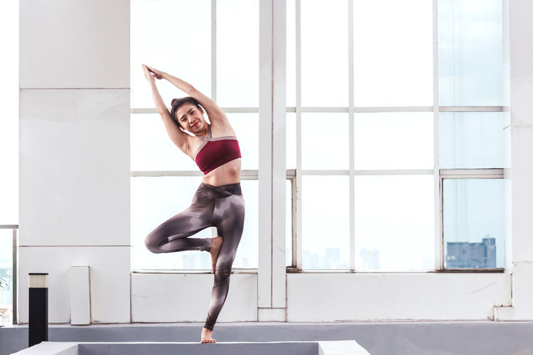 Woman exercising on railing against window