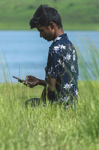 Side view of young man using mobile phone in field