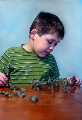 Yong boy plays war with toy soldiers