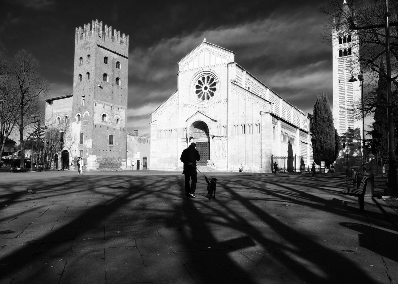 Man with dog walking on street by historic church against sky