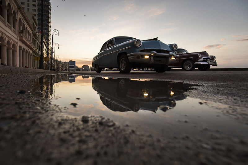 Reflection of building in puddle on road against sky