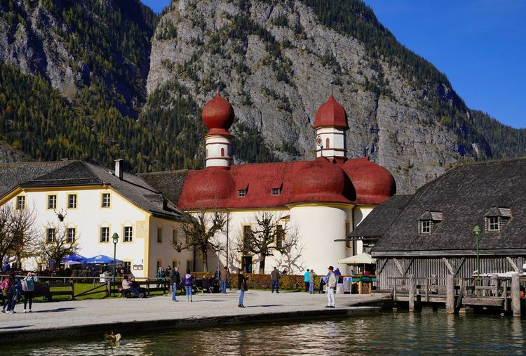 Architecture Building Exterior Building Water Tree Group Of People Nature Day Plant Mountain Sky Incidental People Transportation House City Place Of Worship Religion Outdoors Königssee Hirschau Boathaus Red Blue Sky Chapel Holiday Moments