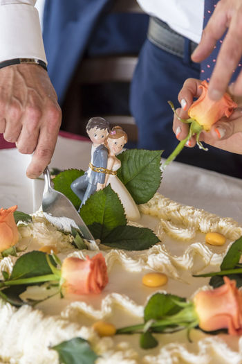 Midsection of man cutting wedding cake