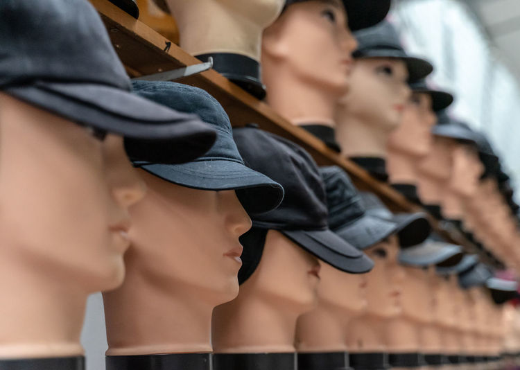 Close-up of mannequins wearing black cap in row at store