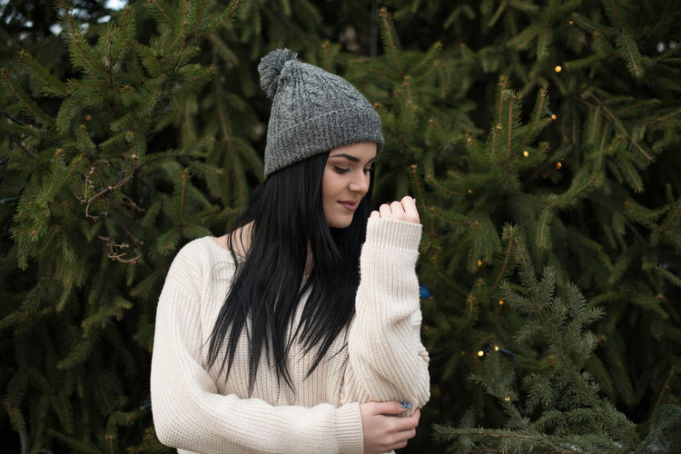 Young woman standing against christmas trees