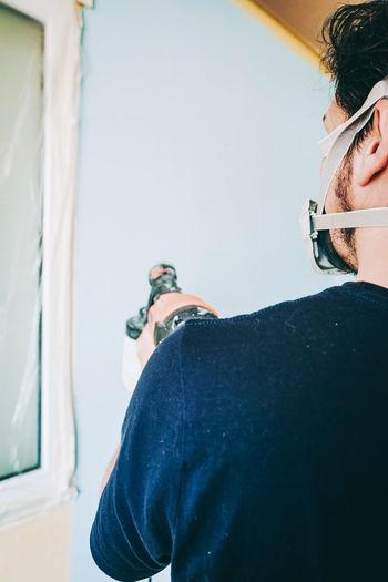 Rear view of young man looking at camera