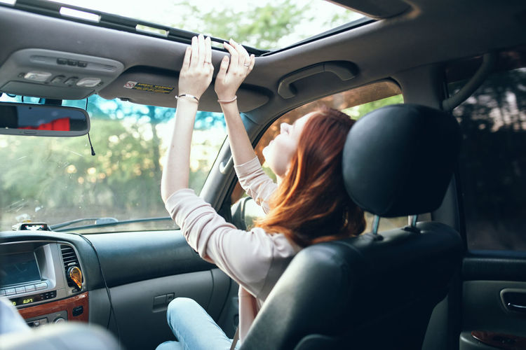 Rear view of woman sitting in car