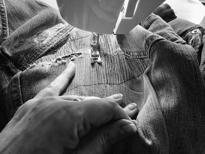 Close-up of woman stitching jeans on sewing machine