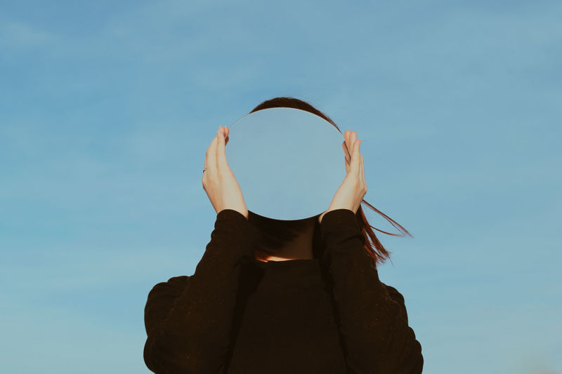 Low angle view of young woman holding mirror against blue sky